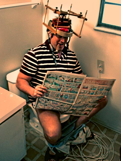 OverMachoGrande sitting on a toilet, reading the paper, and using his very first laser helmet!